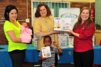 Vera van Dalen receiving product from Samantha van Jaarsveld, Category Manager: Kitchen Appliances for Home of Living Brands with a mom that volunteers at the Nicus Lodge and also a little one